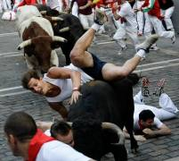 A runner falls on top of a fighting bull as they take the Estafeta curve during the third bull run of the San Fermin festival in Pamplona